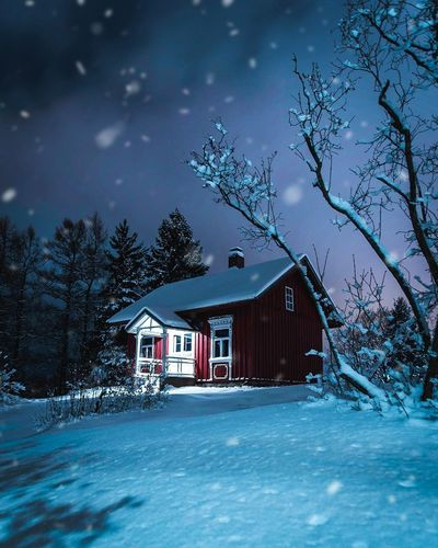 House and trees on snow covered landscape against sky