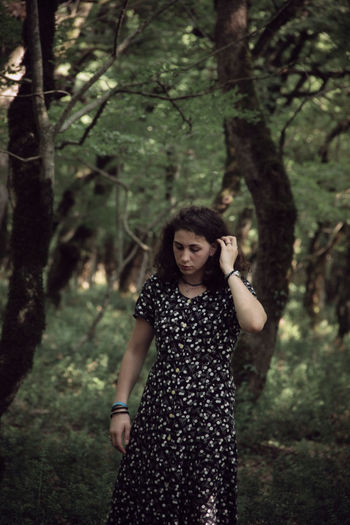 Young woman standing against trees in forest
