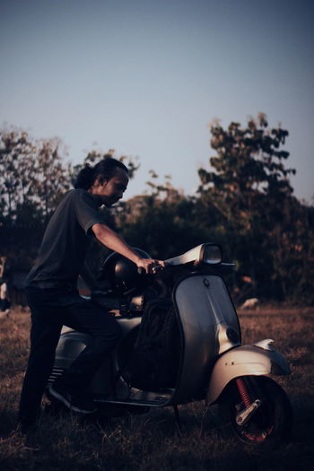 Side view of young man sitting on motorcycle against sky