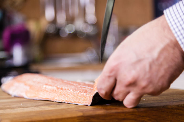 Cropped image of man cleaning fish
