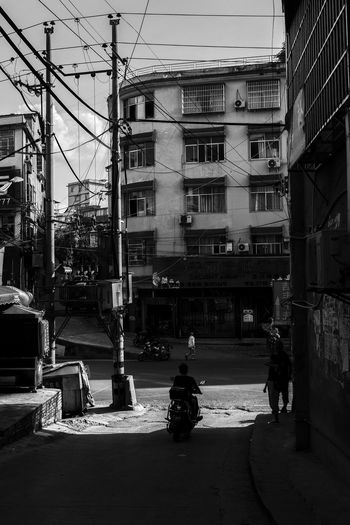 light beside the street Blackandwhite Building Exterior Architecture Built Structure City Transportation Mode Of Transportation The Architect - 2018 EyeEm Awards Street Building City Life Motor Vehicle Road Motor Scooter Day Motorcycle People
