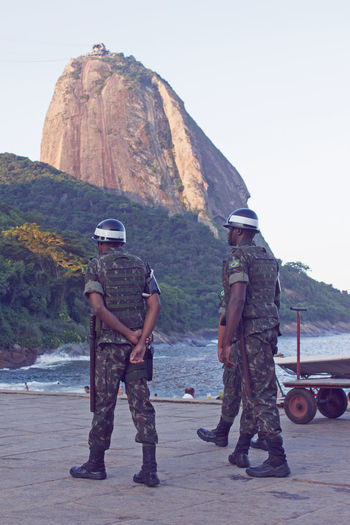 Policemen strolling along Praia Vermelha. Bathing Brazil Beach Men Military Mountain Ocean Police Praiavermelha Real People Rear View Streetphotography Sugarloafmountain Tourism Two People