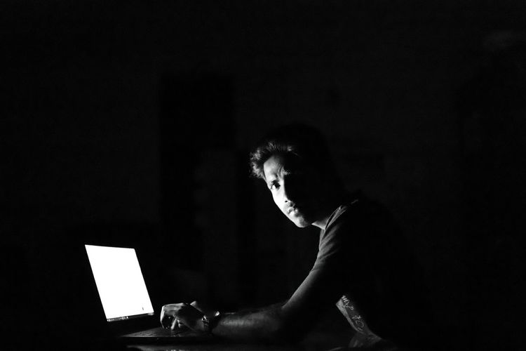 Young man using laptop against black background