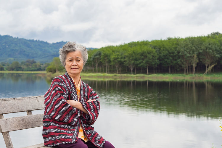 Portrait of smiling elderly woman sitting  by lake against sky