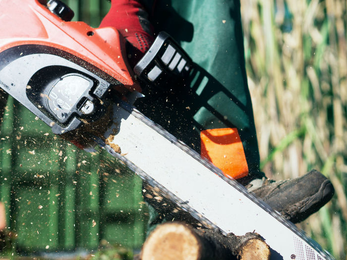 Low section of man sawing wood with chainsaw