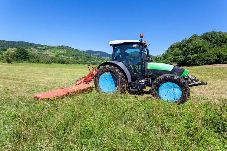 Tractor on field against clear blue sky