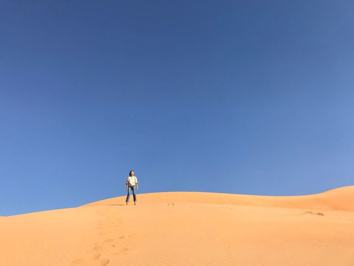Woman standing at desert against clear blue sky