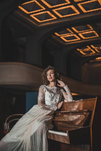 Young Woman In Dress Sitting On Piano