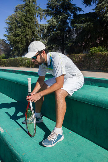 Professional tennis player resting from tennis match on a sunny day. Court Lifestyle Man Set Sitting Tennis Thirst Beard Fresh Game Health Hydrate  Leisure Activity Match One Person Outdoors Pause Player Rest Resting Shadow Sport Sportswear Stop Water