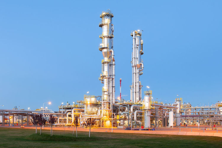 Illuminated factory against clear blue sky