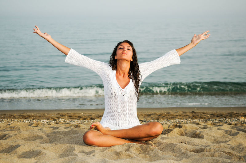 Young Woman Practicing Yoga On Sand At Beach