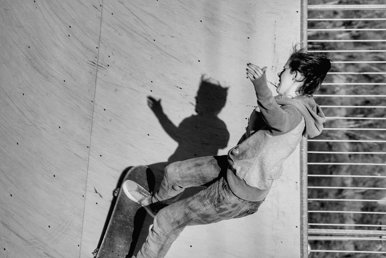 Young Woman Skateboarding On Ramp At Park During Sunny Day