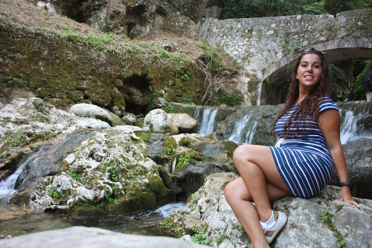 Girl summer vacation in the mountains at river in candalla falls under rock bridge in tuscany lucca