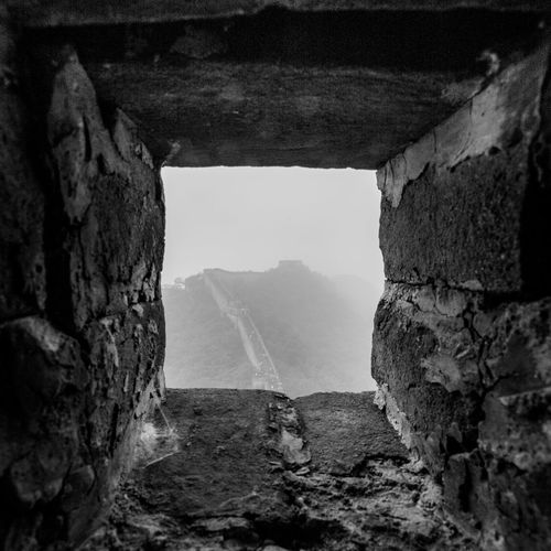 Mountain in foggy weather seen through window in great wall of china