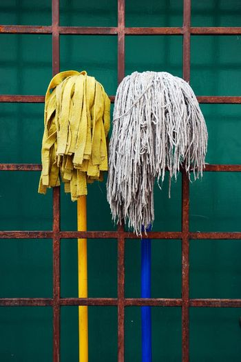 Brooms amidst metal fence