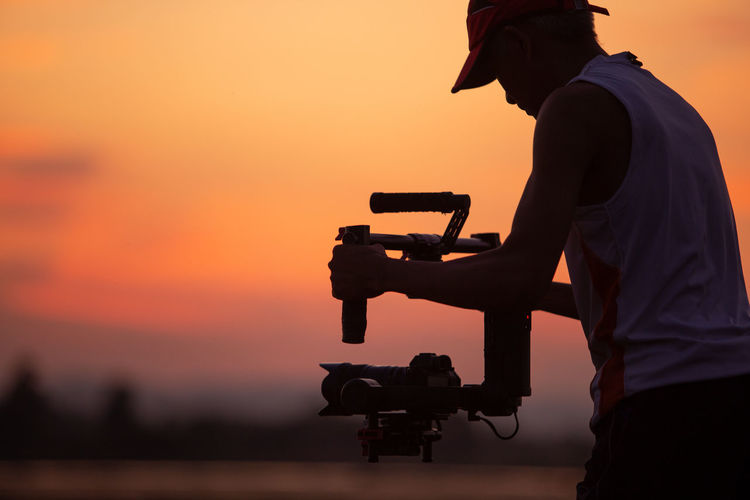 Silhouette man photographing working against sky during sunset