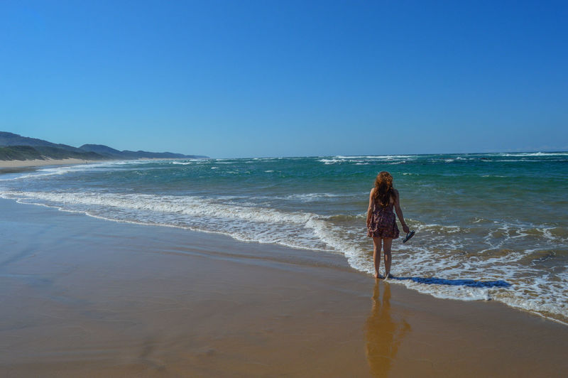 Rear view of woman standing on shore against clear blue sky at beach