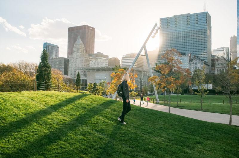 Woman walking in millennium park against modern buildings in city