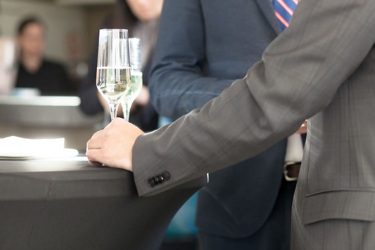 businessman at cocktail party Beverage Bubbly Celebration Cocktail Gathering Lifestyle Suites Anniversary Bar Businessman Drink Drinking Friendship Hand Occasion Party Socializing Special Success Team Tie Together Unrecognizable White Wine
