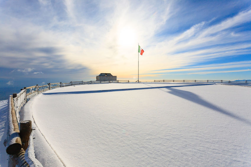 Monte Grappa first world war memorial Incidental People Horizon Over Water Sky Flag Cloud - Sky Nature Water Patriotism Sea Land Scenics - Nature Beauty In Nature Horizon Day Outdoors Sunlight Travel Wind Monte Grappa First World War Architecture Architecture_collection Built Structure Building Exterior Snow