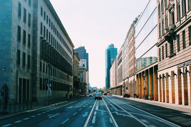 Road amidst city against clear sky