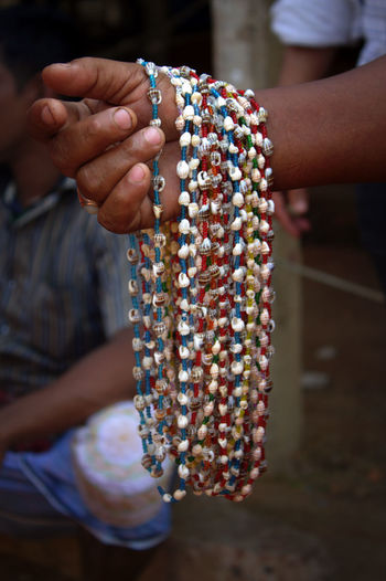Cropped Hand Of Person Holding Bead Necklaces