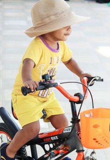 Boy riding bicycle on footpath