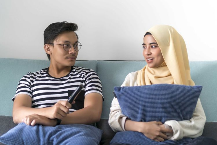Young Malay Couple at the Sofa watching tv together Young Adult Sitting Two People Casual Clothing Young Men Front View Young Women Indoors  Three Quarter Length Togetherness Lifestyles Leisure Activity Men Real People Friendship Adult Furniture Communication Holding Teenager