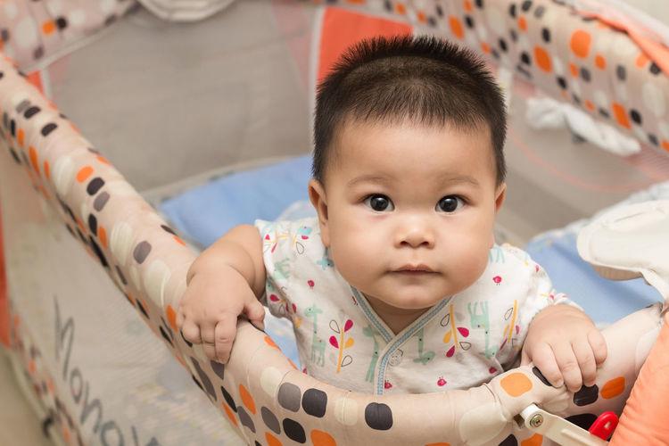 Portrait of cute baby in crib