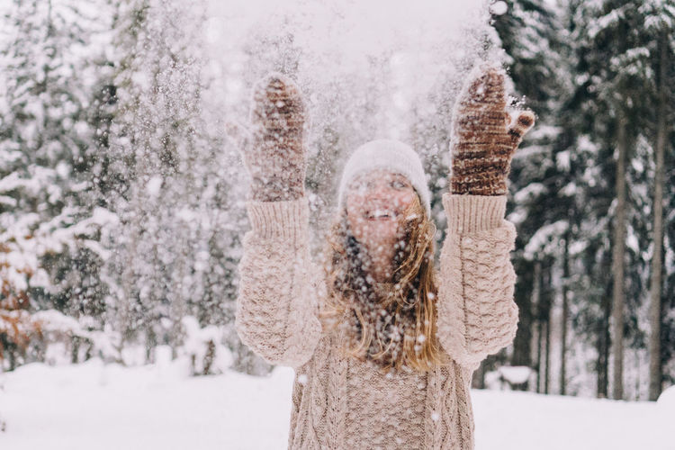 Portrait of smiling woman standing on snow covered trees during winter