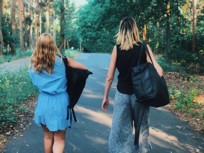 Two woman walkin Two Women Two People Rear View Walking Plant Two People Togetherness Real People Girls Day Adult Nature Females People Casual Clothing Tree Leisure Activity
