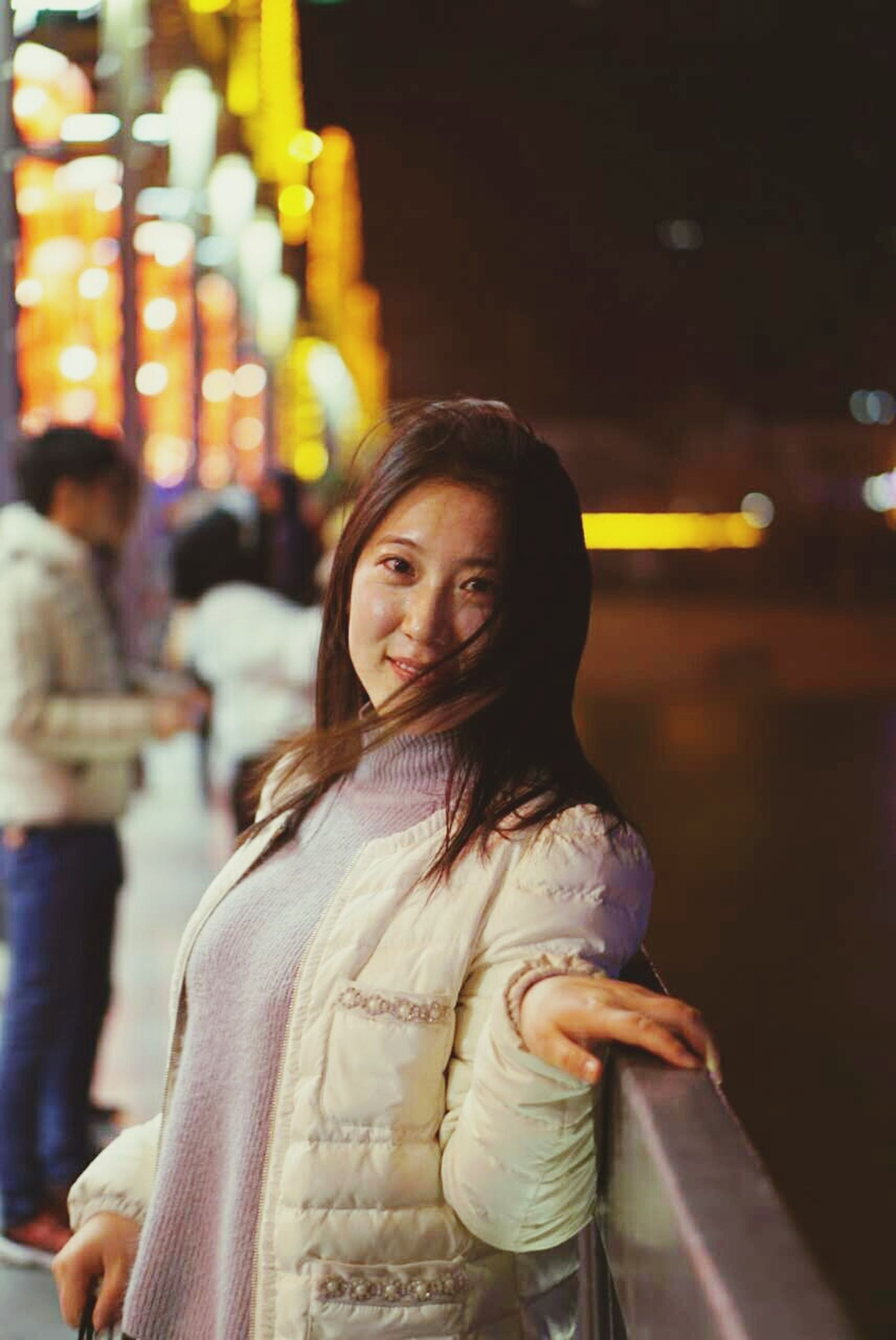 lifestyles, young adult, person, casual clothing, focus on foreground, front view, leisure activity, looking at camera, portrait, illuminated, waist up, night, standing, indoors, three quarter length, young women, headshot, smiling