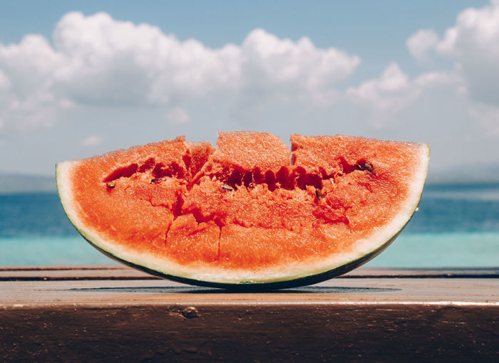 Close-up of fruit on table against sea
