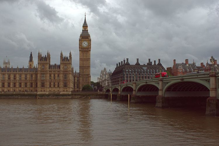 Big ben in front of river thames against cloudy sky