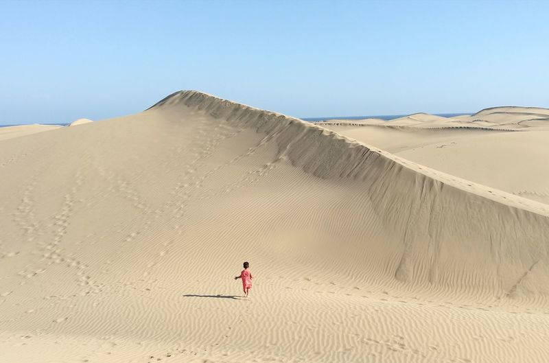 Kid walking on sand at desert