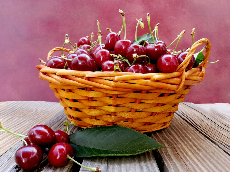 Baskett with cherries on wooden background Still-Life Still Life Food Pink Color Fruit Red Basket Studio Shot Close-up Cherry