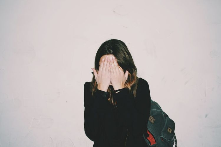 Woman covering face with hands standing against wall
