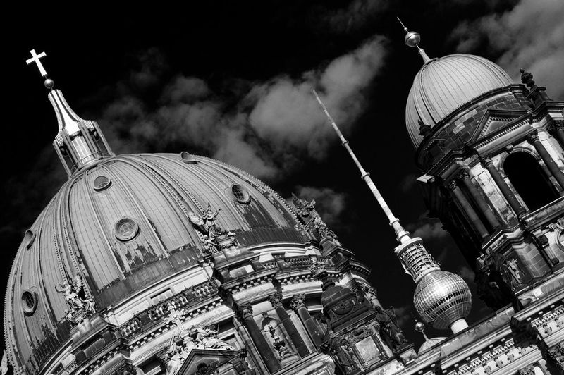 Tilt image of berlin cathedral and fernsehturm tower against sky in city