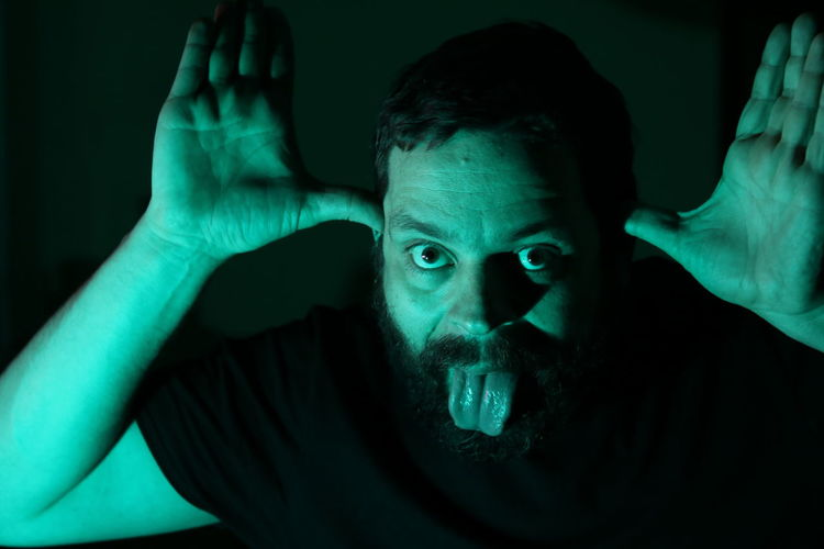 Portrait Of Man Gesturing While Sticking Out Tongue Against Black Background