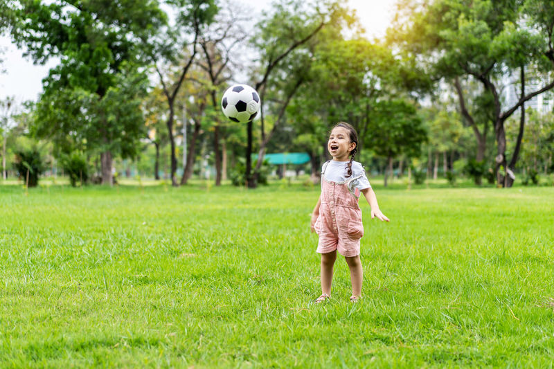 Full length of girl playing with ball on grass