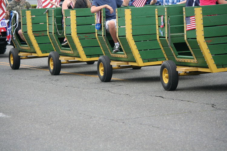 People sitting in vehicle trailer on street during independence day parade