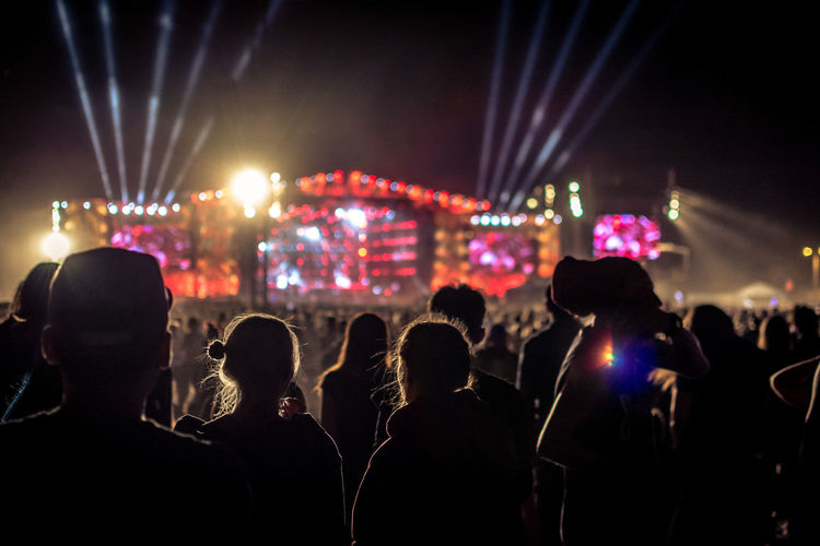 Group Of People Crowd Night Large Group Of People Real People Illuminated Arts Culture And Entertainment Performance Men Music Enjoyment Rear View Event Lighting Equipment Stage - Performance Space Stage Women Audience Nightlife Festival Stage Light Light Positive Emotion Music Festival Excitement