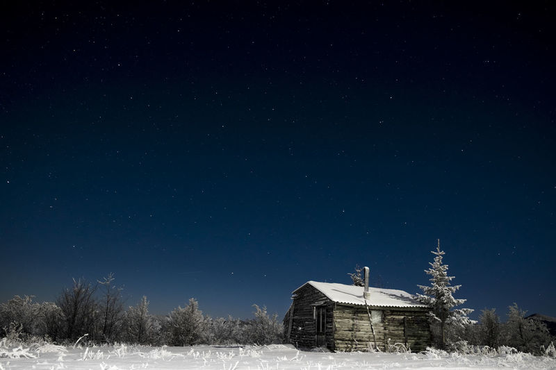 Barn On Snow Covered Field Against Sky At Night