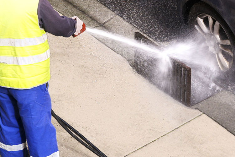 sewer line drainage by professional workers with hose and pressurized water of service truck Sewer Cleaning Drain Pump Sewage Truck Pipe Waste Clogged LINE Industry Service Professional Utility Worker City Canalitation Water Pressure
