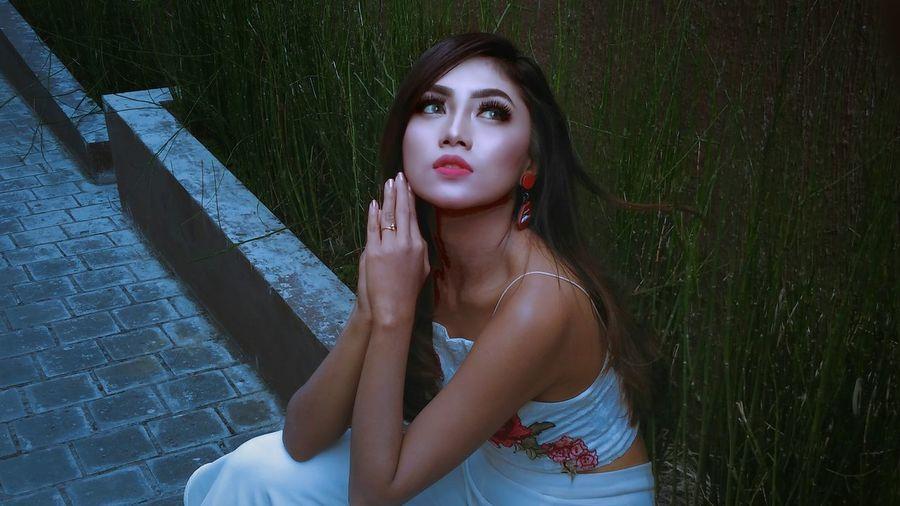 Beautiful young woman sitting on sidewalk