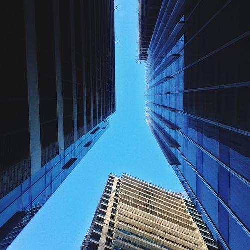 Directly Below Shot Of Modern Buildings Against Clear Blue Sky
