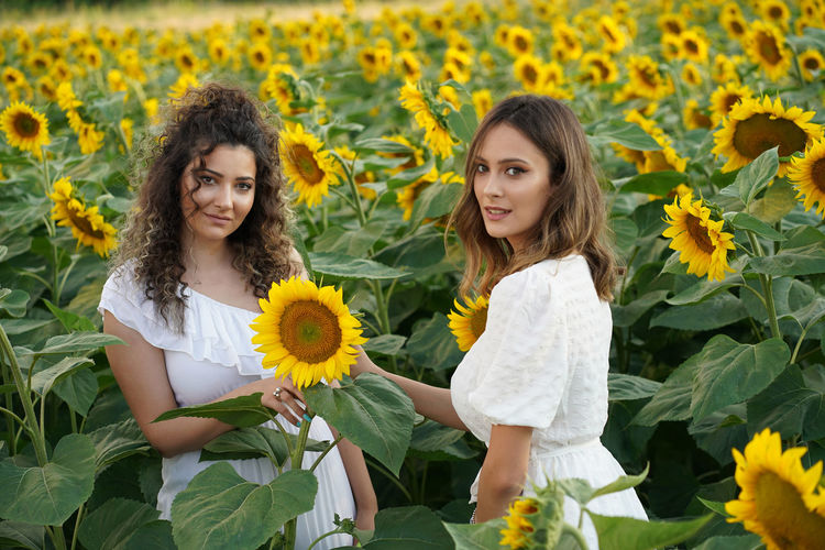 Portrait of smiling friends standing on sunflower field against sky