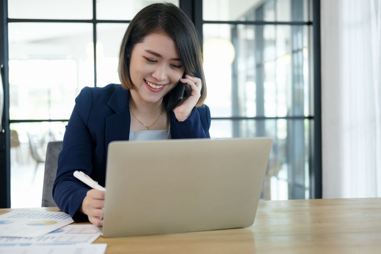 Mid adult woman using phone while sitting on table