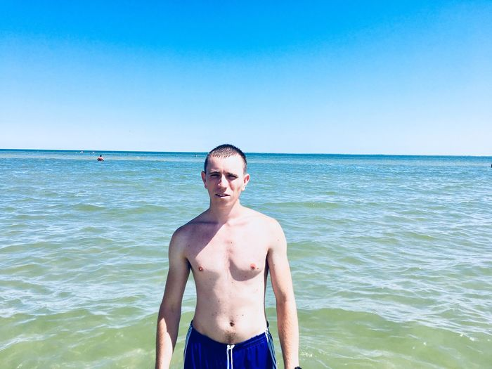 EyeEm Selects Sea Sky Water Standing Beauty In Nature Beach Horizon Over Water Leisure Activity Clear Sky One Person Nature Copy Space Land Horizon Blue Front View Day Scenics - Nature Shirtless Outdoors