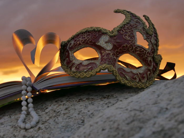 Close-up of masquerade mask with book during sunset